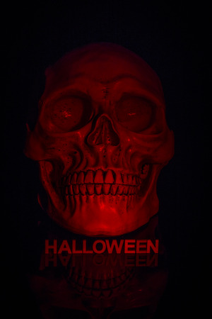 Close up of skull with letters below spelling out the word halloween and lit by a red light to give a spooky red glowing skull on a black background Imagens