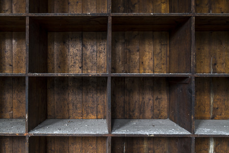 An old and distressed, dark wood shelf. Made of empty boxes covered with dust and dirt.