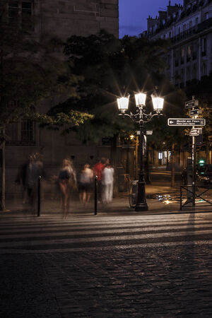 Shadowy and blurred men and women on zebra crossing at night on an urban street. Imagens