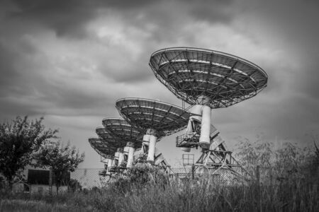 Radio telescope satellite dish array in a barley field before a storm in black and white photo
