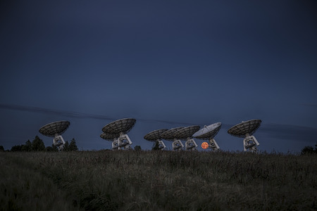 The full moon rises over the horizon behind a radio telescope array as the sun sets on the opposite horizon giving the moon an orange glow.