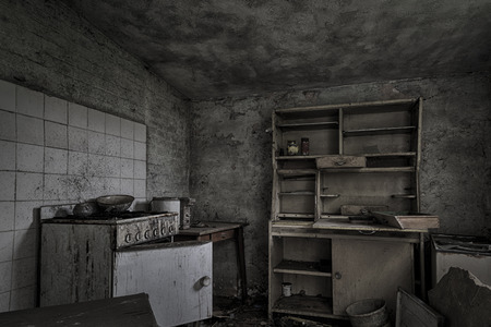 A dark, shabby kitchen in a dilapidated, abandoned house.