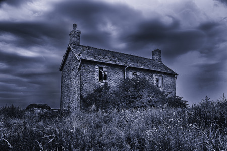 residential house: Spooky, haunted, derelict house with broken windows under a stormy sky. Black and white with a blue tint effect.