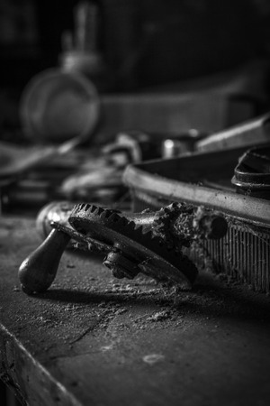 Rusty, old hand drill on dusty cobweb workbench in monochrome Imagens