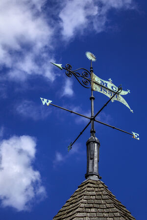 Weather vane on a sunny blue sky with white fluffy clouds. Wind direction arrow points west and has a slight green patina on the copper finial