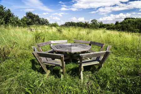 Blue sky with white fluffy clouds and a weathered wooden picnic table in uncultivated meadow in summer