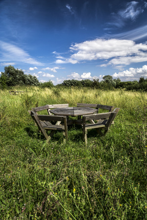 uncultivated: Blue sky with white fluffy clouds and a weathered wooden picnic table in uncultivated meadow in summer