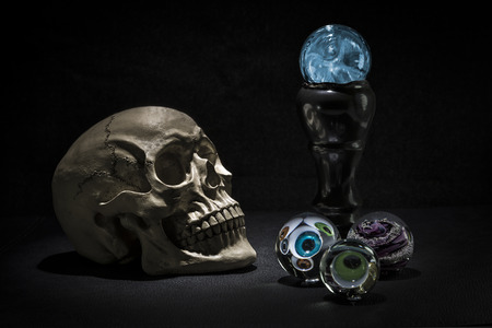 Dark and shadowy human skull in a pool of light. Crystal balls with eyeballs looking out Imagens