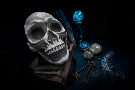 Human skull on book in a pool of light. Crystal balls glowing and cloudy. Spilled glass jar and two rusty old keys. Weird wide angle and Dutch angle for spooky effect.