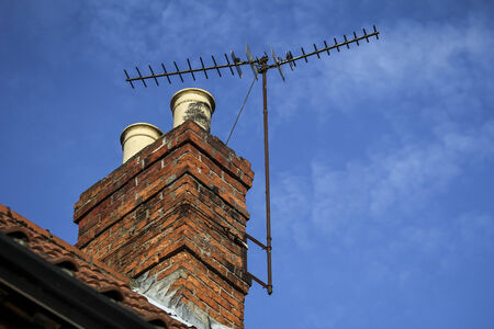 Chimney on a roof of a house with terrestrial freeview television aerial and blue sky with light cloud
