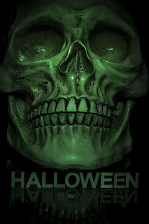 Close up of skull with letters below spelling out the word halloween and lit by a green light to give a spooky green glowing skull on a black background