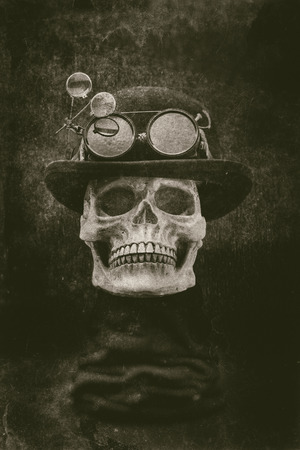 steampunk goggles: A spooky looking skull wearing a bowler hat, goggles with loupe attached in a steampunk style. The photo has a distressed, antique grunge effect. Stock Photo