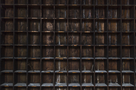 Wide view of an old and distressed, dark wood shelf. Square boxes covered with dust and dirt. Most are empty but a few still have rusty tools in them. Imagens