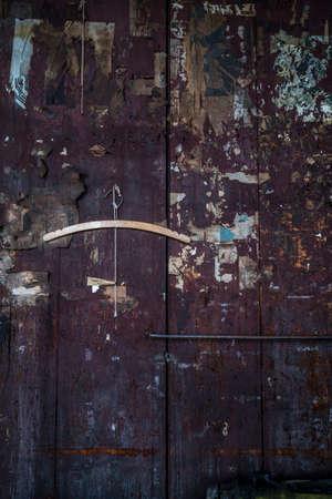 clippings: Tablas de madera con la pintura descascarada, quemado, acuchillado y destrozado recortes newpaper ilegibles y un gancho de ropa al azar Foto de archivo