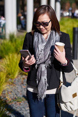 sunny day: Female walking with coffee looking at phone