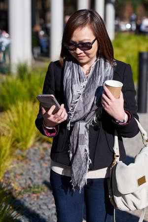 dia soleado: Mujer caminando con el café que mira el teléfono