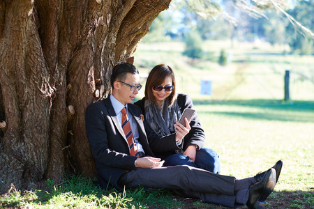 asian adult: couple sitting under tree on sunny date Stock Photo