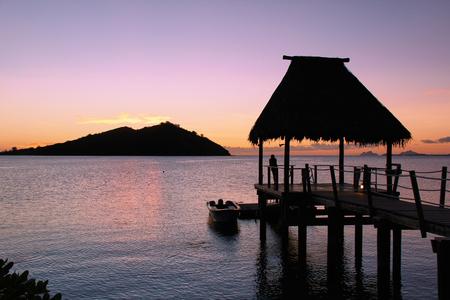fiji: lone silhouette on jetty at sunset in Fiji