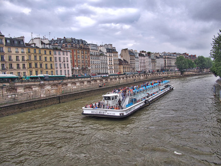 dinner cruise: Paris, France, Europe - June 21, 2013: Sightseeing Tourist boat Bateaux-Mouches with passengers on board cruising along the Seine River in Paris, France. Tour buses parked along the left side of the river, and people walking along the river. Editorial