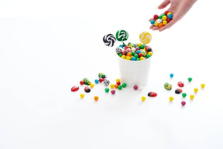 overflowing: female hand dropping candy into an overflowing bucket of candy Stock Photo