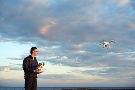 recreational: man flying a quadcopter with remote control at the beach at sunset