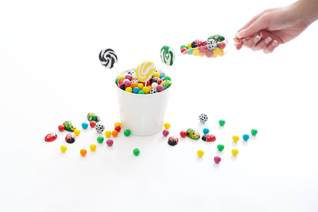 overflowing: female hand holding a scoop of candy with a overflowing bucket of candy Stock Photo