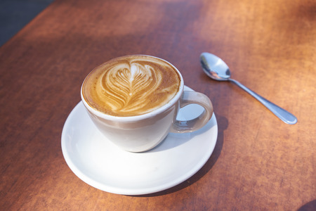 coffee table: coffee in white cup with coffee art on wooden table Stock Photo