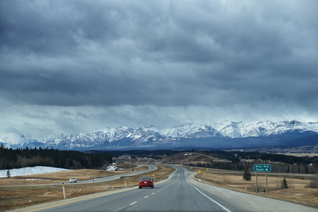 storm clouds: Road to Banff in winter with storm clouds and Canada Rocky Mountain on the horizon Stock Photo