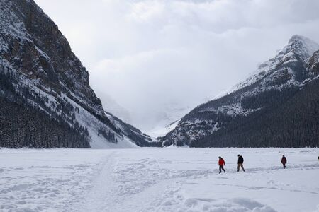 unrecognisable people: people walking on the frozen Lake Louise in winter