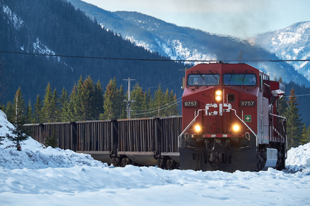 goods train: Banff, Canada - March 18, 2014: Canadian Pacific train coming round the bend with Canadian Rockies in the background in winter