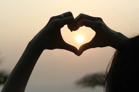 Hands make heart at sunrise Stock Photo