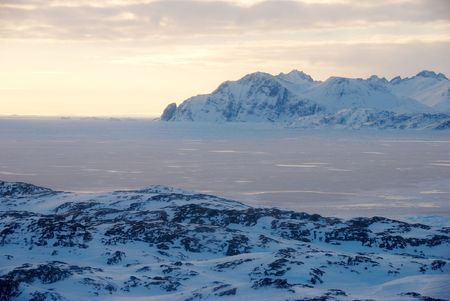moutains: Flying over ice field and moutains at sunset, Greenland Stock Photo