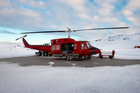 greenland: A red helicopter landing with mountains in background, Greenland