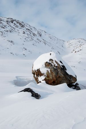 moutains: A big snow-covered boulder with moutains in background, Greenland