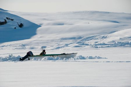 A fisher in his motorboat waiting on icefield photo