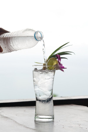 Pouring water into a glass that is adorned with flowers. photo