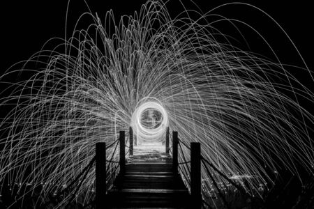 light trails: Abstract Image of Burning Wirewool being used to make circle like light trails at Night. Black and White Stock Photo