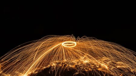 burning time: Abstract Image of Burning Wirewool being used to make circle like light trails at Night Stock Photo