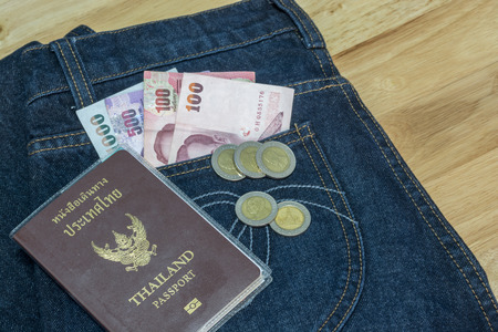 customs official: Thailand passport with Thai money ready to travel On the background Jeans Stock Photo