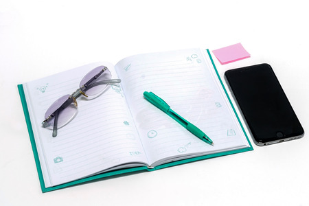 jot: notebook, smartphone, eye glasses, and pen, On a white background Stock Photo