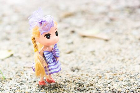 Dolls with Wearing a purple dress Blond hair on the sand.