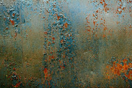 rusty background: Damaged paint on the metal. Old cracked paint pattern on rusty background.