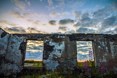 Wall of a ruined house on sunset sky background Stock Photo