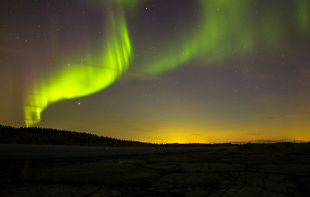 ionosphere: Autumn Northern lights over the highway Stock Photo
