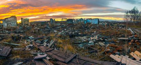 De overblijfselen van verwoeste huizen bij zonsondergang