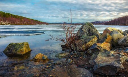 The Northern nature in the spring.Forest lake covered with melting ice Stock Photo