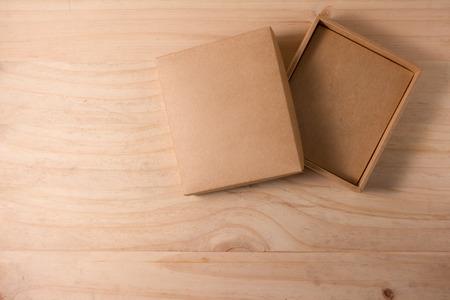 木製の背景に段ボール箱を開けてください。
