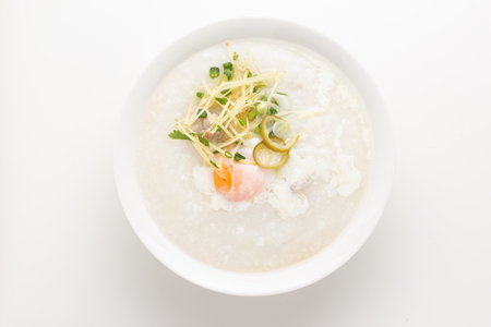 Asian congee with minced pork and egg in white bowl. 스톡 콘텐츠