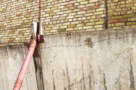cement solution: concrete fence near a brick wall with barbed wire propped pipe Stock Photo