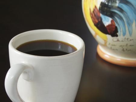 Freshly Brewed Coffee in a white mug  Cookie jar in background  Displayed on dark table top  photo